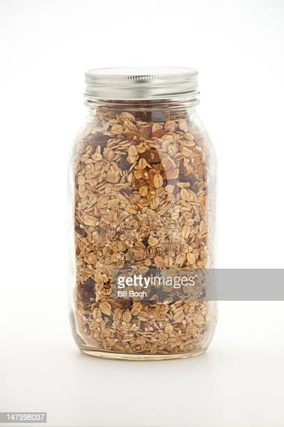 jar of homemade granola on white - rolled oats stock photos and pictures