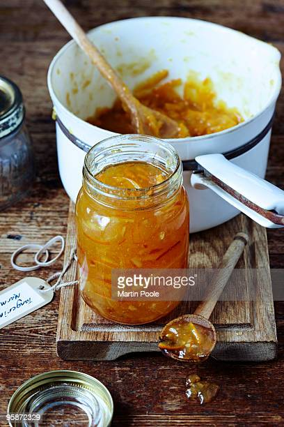 Jar of marmalade on table with pan
