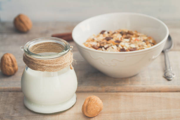 Jar of milk or plain yogurt with a spoon and a white bowl with granola or muesli in the background. Healthy breakfast top view composition