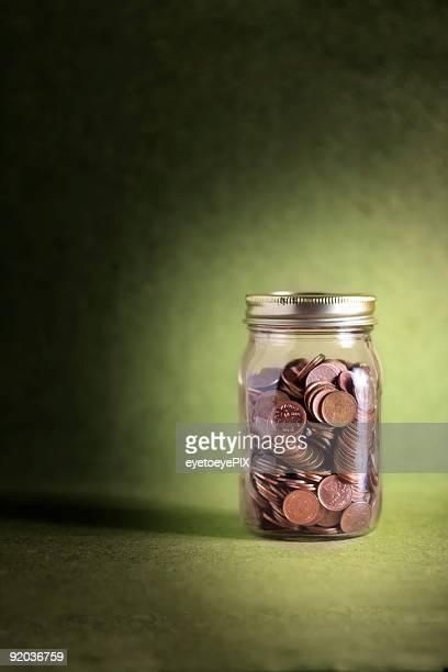 Jar of pennies on green background (Money Series)