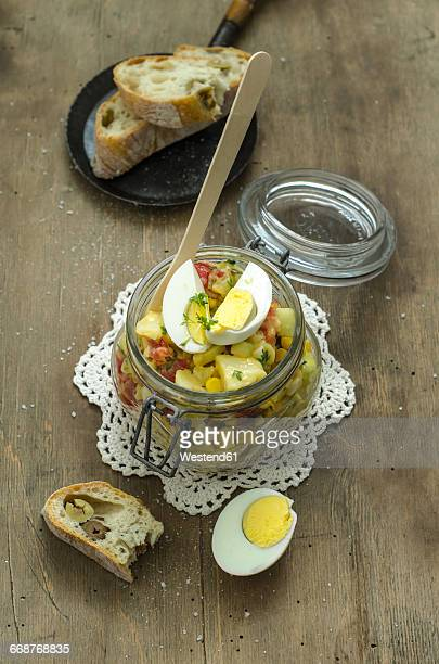 Jar of potato salad with tomatoes, corn, cucumber and eggs