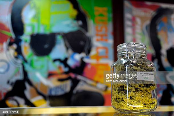 A jar of the marijuana strain Island Sweet Skunk sits on the counter in front of a mural of journalist Hunter S Thompson at Denver Kush Club in...