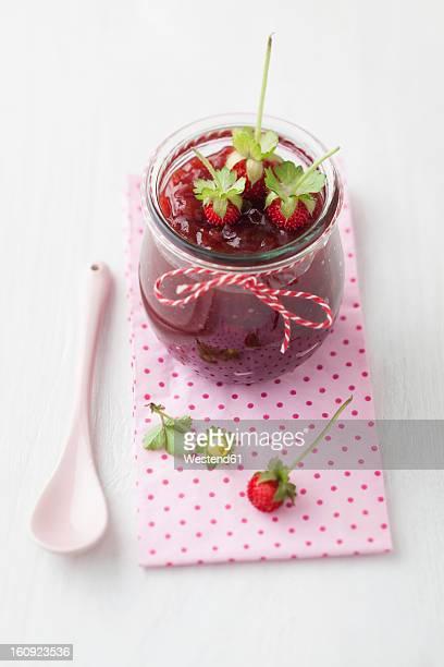 Jar of wild strawberry jam with spoon on white background