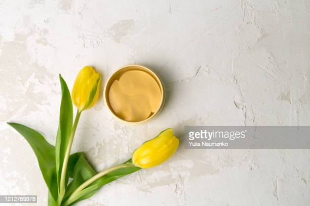 jar of yellow cosmetic patches for skin under eyes next to delicate tulips flowers on light background, minimal flat lay composition. - face mask beauty product stock pictures, royalty-free photos & images