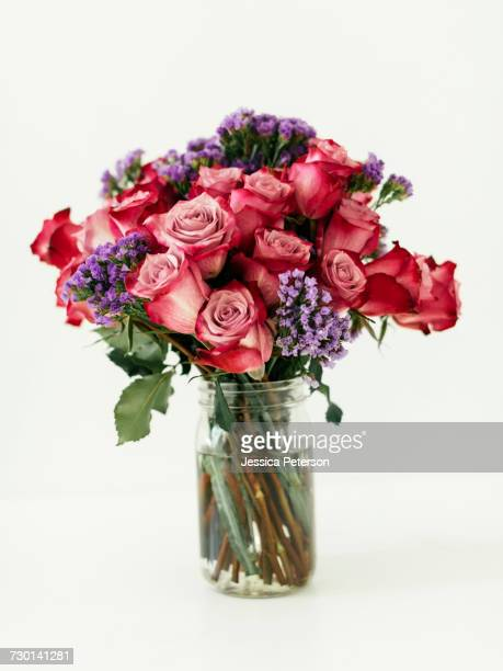 jar with bouquet of red roses - purple roses bouquet ストックフォトと画像