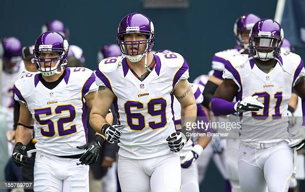 Jared Allen of the Minnesota Vikings takes the field with Chad Greenway of the Minnesota Vikings and D'Aundre Reed of the Minnesota Vikings before a...