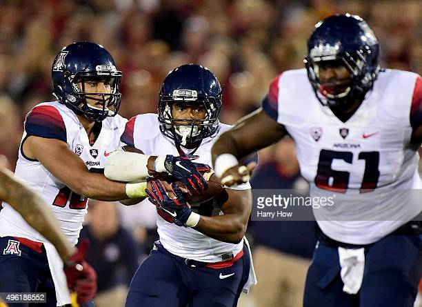 Jared Baker of the Arizona Wildcats takes a hand off from Anu Solomon as he follows the block of Cayman Bundage during the first quarter against the...