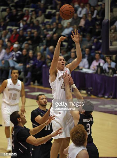 Jared Berggren of the Wisconsin Badgers shoots over Tre Demps Mike Turner and Dave Sobolewski of the Northwestern Wildcats at WelshRyan Arena on...