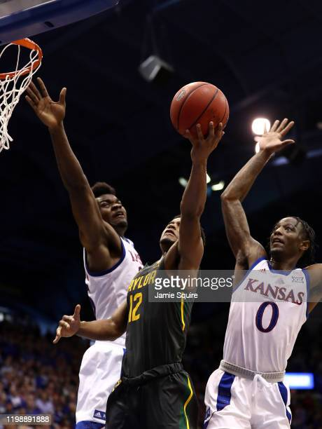 Jared Butler of the Baylor Bears shoots as Udoka Azubuike and Marcus Garrett of the Kansas Jayhawks defend during the game at Allen Fieldhouse on...