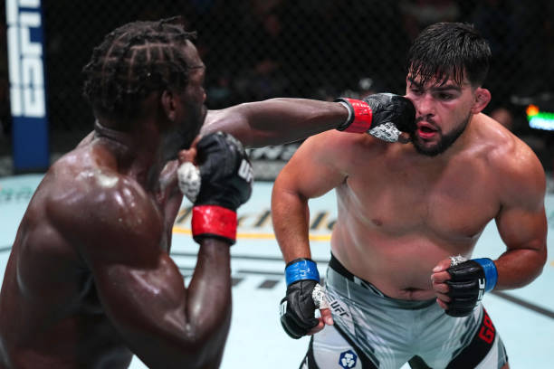 Jared Cannonier punches Kelvin Gastelum in a middleweight fight during the UFC Fight Night event at UFC APEX on August 21, 2021 in Las Vegas, Nevada.