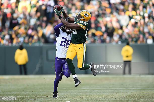 Jared Cook of the Green Bay Packers catches a pass in front of Trae Waynes of the Minnesota Vikings during the second half of a game at Lambeau Field...