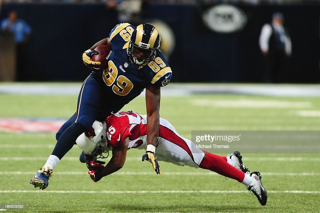 Jared Cook #89 of the St. Louis Rams is tackled by Jerraud Powers #25 of the Arizona Cardinals at the Edward Jones Dome on September 8, 2013 in St. Louis, Missouri.