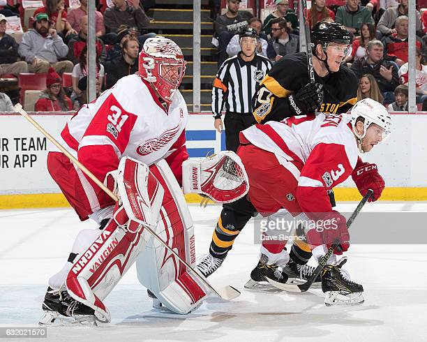 Jared Coreau of the Detroit Red Wings follows the play as teammate Nick Jensen battles for position with Riley Nash of the Boston Bruins during an...