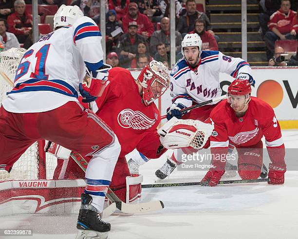 Jared Coreau of the Detroit Red Wings makes a glove save as teammate Nick Jensen defends against Mika Zibanejad of the New York Rangers during an NHL...