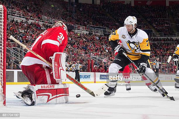 Jared Coreau of the Detroit Red Wings makes a save as Matt Cullen of the Pittsburgh Penguins looks for the rebound during an NHL game at Joe Louis...
