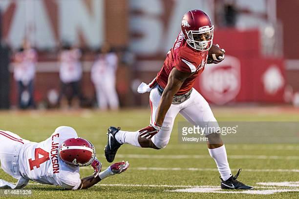 Jared Cornelius of the Arkansas Razorback stiff arms and breaks the tackle of Eddie Jackson of the Alabama Crimson Tide at Razorback Stadium on...