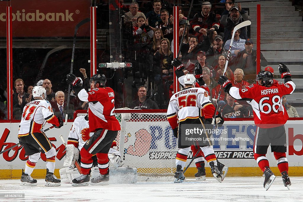 Jared Cowen #2 of the Ottawa Senators celebrates his third period goal along with Mike Hoffman #68 against Karri Ramo #31, Chad Billins #41 and Tyler Wotherspoon #56 of the Calgary Flames during an NHL game at Canadian Tire Centre on March 30, 2014 in Ottawa, Ontario, Canada.