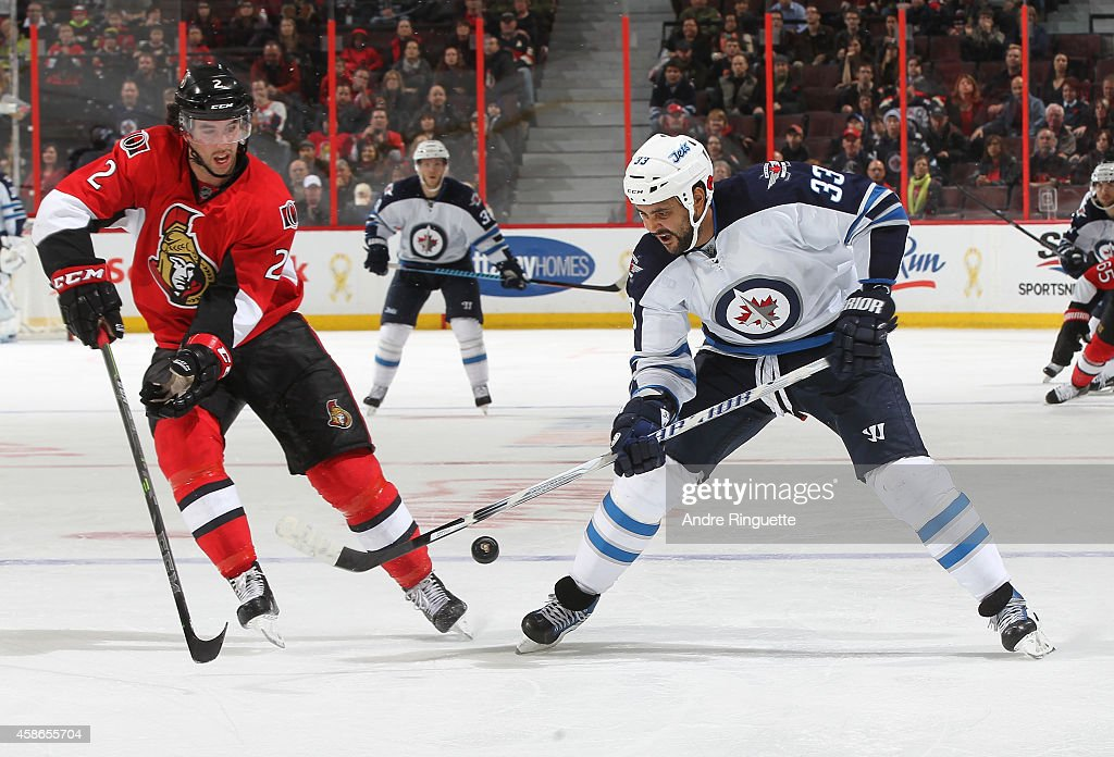 Jared Cowen #2 of the Ottawa Senators defends against a pass by Dustin Byfuglien #33 of the Winnipeg Jets at Canadian Tire Centre on November 8, 2014 in Ottawa, Ontario, Canada.