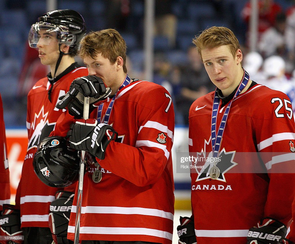 Jared Cowen #2, Sean Couturier #7 and Carter Ashton #25 of Canada stand on the ice during medal ceremonies after losing to Russia 5-3 during the 2011 IIHF World U20 Championship Gold medal game between Canada and Russia at the HSBC Arena on January 5, 2011 in Buffalo, New York.