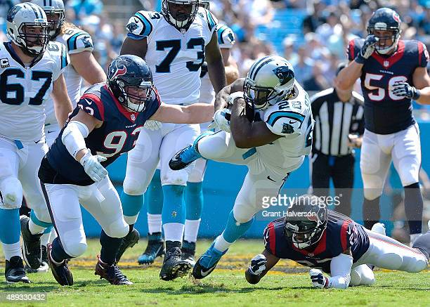 Jared Crick of the Houston Texans tackles Jonathan Stewart of the Carolina Panthers during their game at Bank of America Stadium on September 20,...