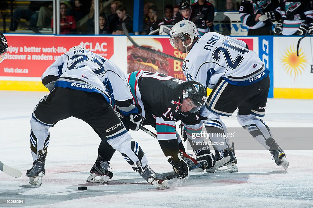 Jared Dmytriw #27 and Logan Fisher #20 of Victoria Royals check Dillon Dube #19 of Kelowna Rockets on OCTOBER 9, 2015 at Prospera Place in Kelowna, British Columbia, Canada.