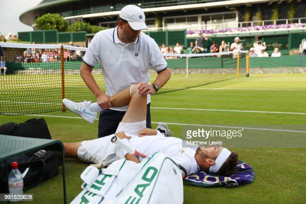 Jared Donaldson of the United States is treated for an injury during his Men's Singles second round match against Stefanos Tsitsipas of Greece on day...