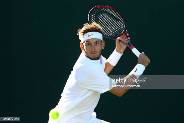 Jared Donaldson of the United States returns against Malek Jaziri of Tunisia on day one of the Wimbledon Lawn Tennis Championships at All England...