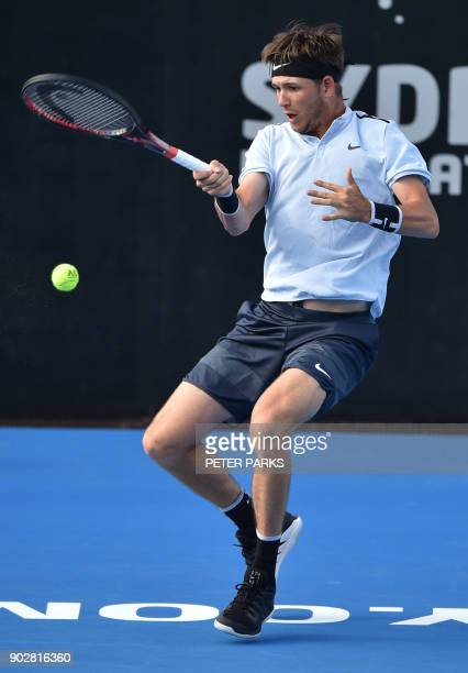 Jared Donaldson of the US hits a return Gilles Simon of France in their men's singles first round match at the Sydney International tennis tournament...