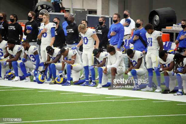Jared Goff, Cooper Kupp and Josh Reynolds of the Los Angeles Rams stand as their teammates kneel during the national anthem before their game against...