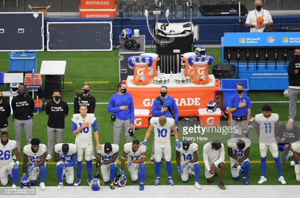 Jared Goff, Cooper Kupp and Josh Reynolds of the Los Angeles Rams stand as their teammates kneel during the national anthem before the game against...