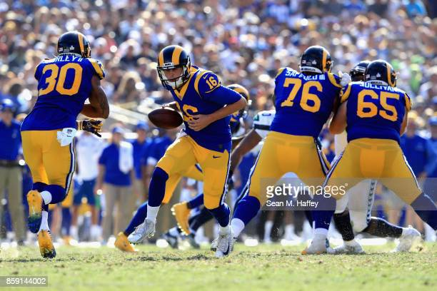 Jared Goff hands off to Todd Gurley as Rodger Saffold and John Sullivan of the Los Angeles Rams block uring the second half of a game against the...