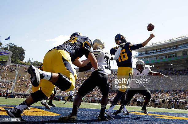 Jared Goff of the California Golden Bears passes the ball while pressured by Kenneth Olugbode and Derek McCartney of the Colorado Buffaloes at...