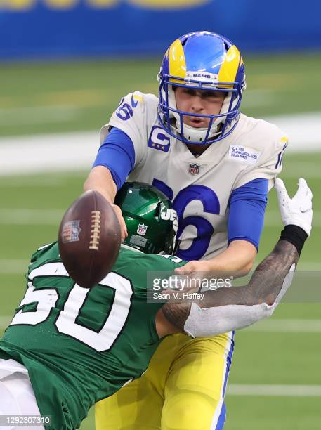 Jared Goff of the Los Angeles Rams is hit by Frankie Luvu of the New York Jets during the second quarter of a game at SoFi Stadium on December 20,...