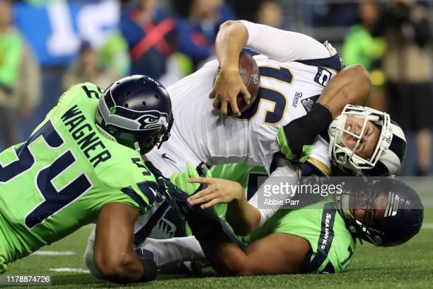 Jared Goff of the Los Angeles Rams is stopped for an unsuccessful two point conversion attempt by Bobby Wagner and Al Woods of the Seattle Seahawks...