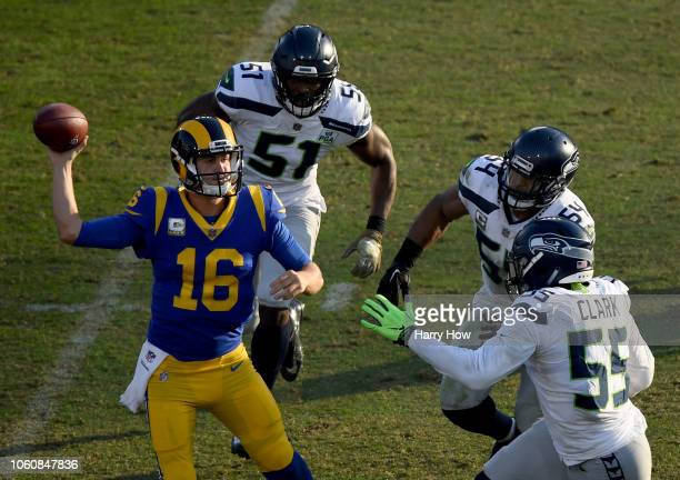 Jared Goff of the Los Angeles Rams passes as he is rushed by Frank Clark Bobby Wagner and Barkevious Mingo of the Seattle Seahawks in the third...