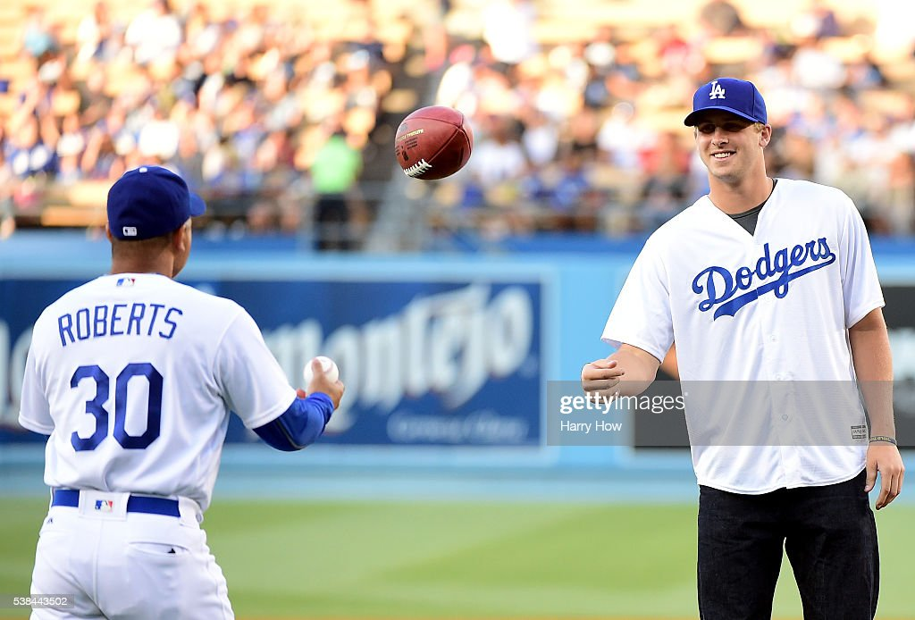 Jared Goff #16 of the Los Angeles Rams tosses a football to manager Dave Roberts #30 prior to throwing out a ceremonial first pitch before the game against the Colorado Rockies at Dodger Stadium on June 6, 2016 in Los Angeles, California.