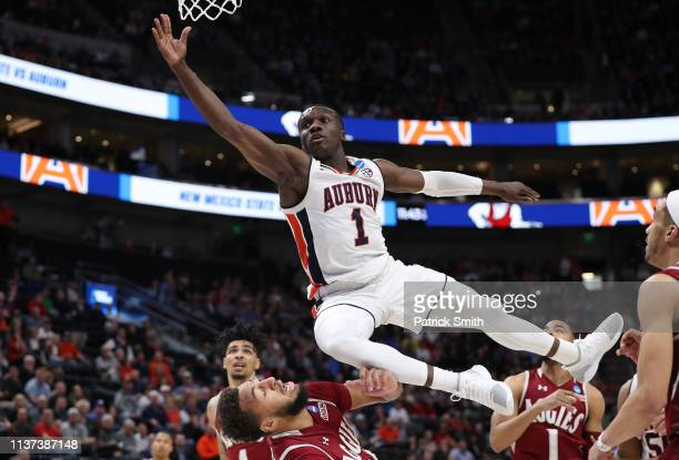 Jared Harper of the Auburn Tigers falls after driving to the basket during the first half against the New Mexico State Aggies in the first round of...