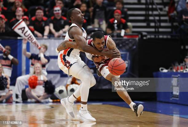 Jared Harper of the Auburn Tigers fouls AJ Harris of the New Mexico State Aggies during the second half in the first round of the 2019 NCAA Men's...