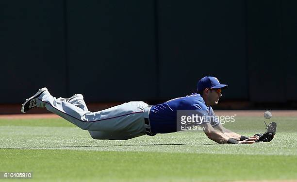 Jared Hoying of the Texas Rangers can not catch a ball hit by Marcus Semien of the Oakland Athletics in the second inning at OaklandAlameda County...