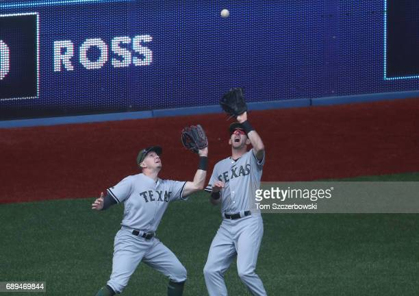 Jared Hoying of the Texas Rangers catches a fly ball while nearly colliding with Ryan Rua in the eighth inning during MLB game action against the...