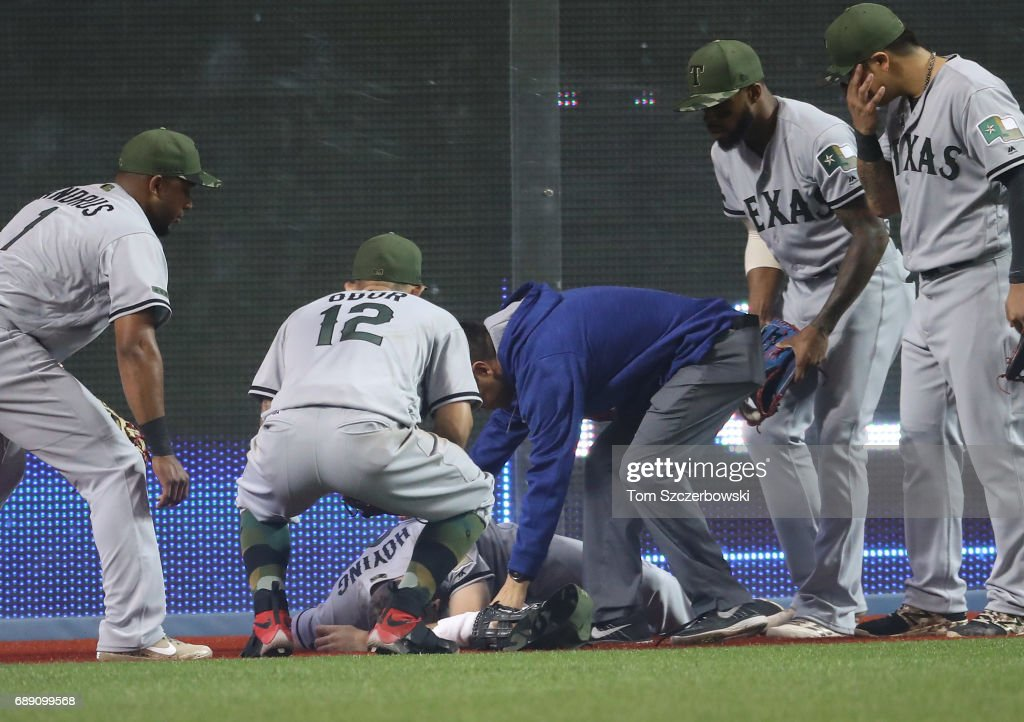 Jared Hoying #31 of the Texas Rangers is tended to by a trainer and teammates after slamming into the wall following a running catch in the fifth inning during MLB game action against the Toronto Blue Jays at Rogers Centre on May 27, 2017 in Toronto, Canada.