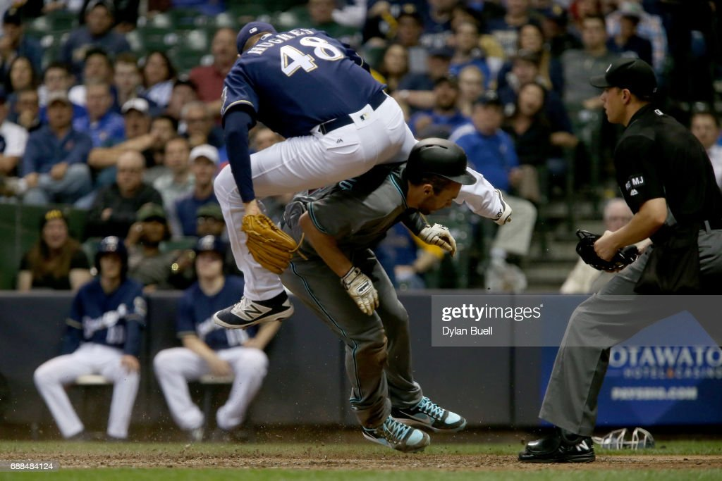 Jared Hughes #48 of the Milwaukee Brewers leaps over Paul Goldschmidt #44 of the Arizona Diamondbacks after Goldschmidt scored a run on a wild pitch in the eighth inning at Miller Park on May 25, 2017 in Milwaukee, Wisconsin.