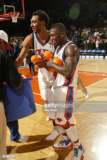 Jared Jeffries and Nate Robinson of the New York Knicks toss mini basketballs to fans after last win of the season against the New Jersey Nets on...