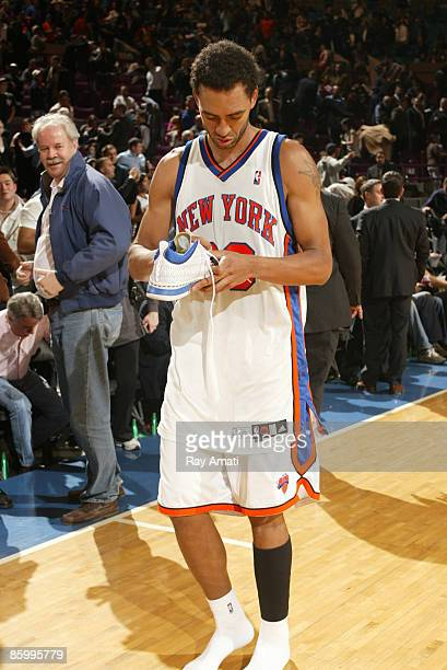 Jared Jeffries of the New York Knicks signs his sneaker before giving it to a fan after win the New Jersey Nets on April 15 2009 at Madison Square...