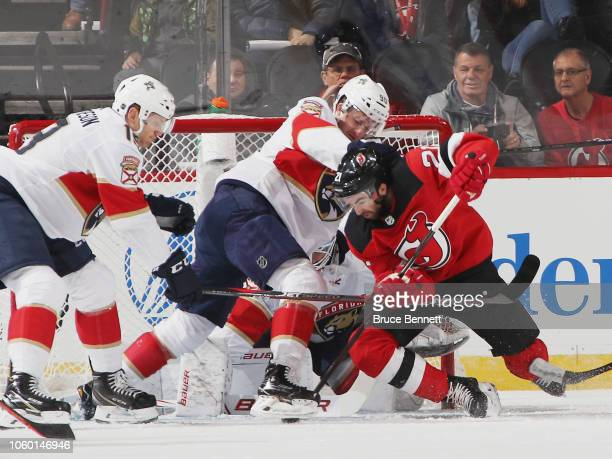 Jared McCann of the Florida Panthers checks Kyle Palmieri of the New Jersey Devils in the crease during the first period at the Prudential Center on...