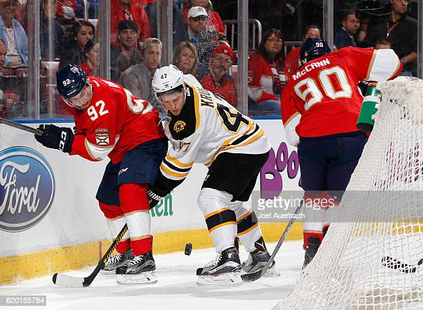 Jared McCann of the Florida Panthers circles behind the net as Kyle Rau of the Florida Panthers and Torey Krug of the Boston Bruins battle for...