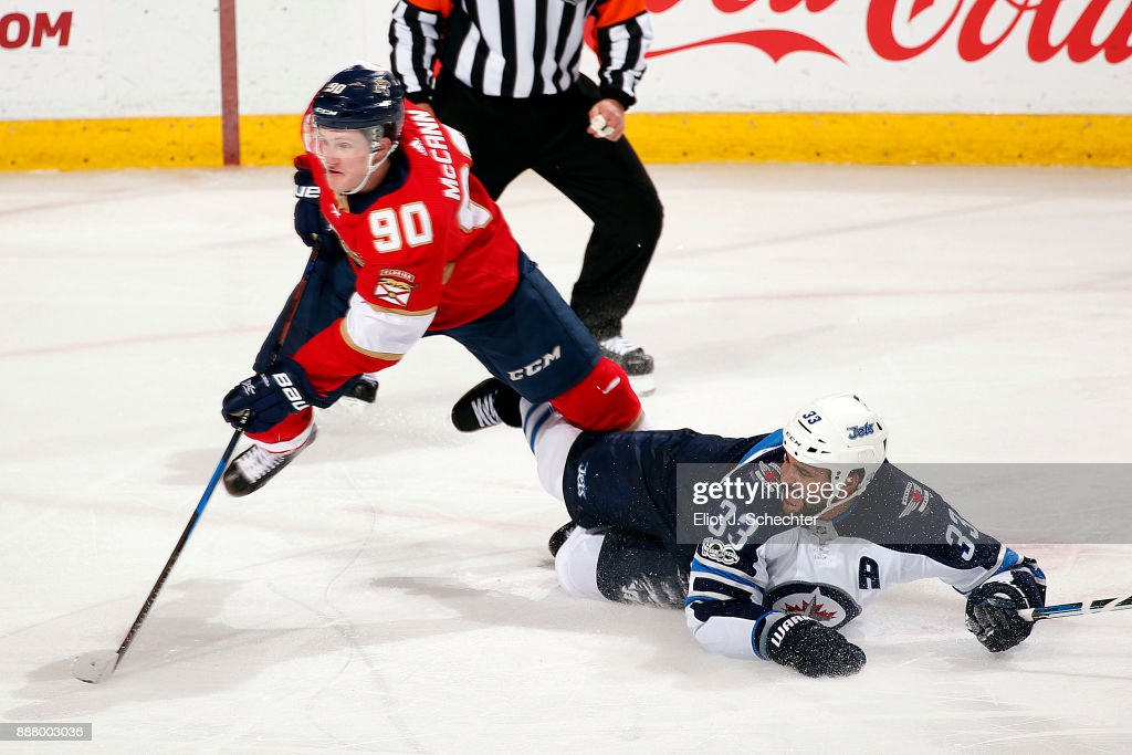 Jared McCann #90 of the Florida Panthers gets tripped up by Dustin Byfuglien #33 of the Winnipeg Jets at the BB&T Center on December 7, 2017 in Sunrise, Florida.