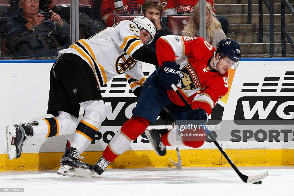 Jared McCann #90 of the Florida Panthers is taken to the ice by Tim Schaller #59 of the Boston Bruins as he attempts to pass the puck during first period action at the BB&T Center on January 7, 2017 in Sunrise, Florida.