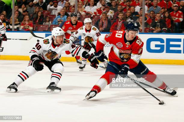 Jared McCann of the Florida Panthers skates with the puck against John Hayden of the Chicago Blackhawks at the BBT Center on November 24 2018 in...