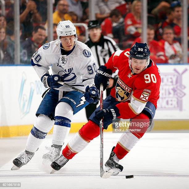 Jared McCann of the Florida Panthers skates with the puck against Vladislav Namestnikov of the Tampa Bay Lightning at the BBT Center on November 7...